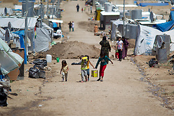 © Licensed to London News Pictures. 12/05/2013. Dohuk, Iraq. Young Syrian refugees carry water back to their tents at a refugee camp in Iraqi-Kurdistan, set up for Syrians escaping the ongoing civil war. The camp, close to the city of Dohuk, now houses in the region of 45,000 refugees, with around 400 new arrivals every day. Photo credit: Matt Cetti-Roberts/LNP