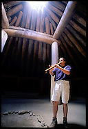 Park guide Dakota Goodhouse plays flute in main Mandan lodge at On-A-Slant Indian Village; Fort Abraham Lincoln State Park; Mandan, North Dakota