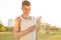 Young jogger listening to music through cell phone in park