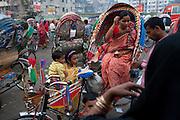 A woman pays a rickshaw driver at the Kamalapur Railway Station in Dhaka, Bangladesh.