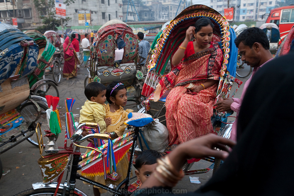 A woman pays a rickshaw driver at the Kamalapur Railway Station in Dhaka, Bangladesh.