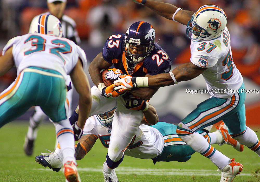 SHOT 11/2/08 6:02:14 PM - Denver Broncos running back Andre Hall (#23, RB) is gang tackled by Miami Dolphins Jason Allen (#32, S), Channing Crowder (#52, LB) and Yeremiah Bell (#37, S) during the fourth quarter of their NFL football game at Invesco Field in Denver, Co. November 2, 2008. The Broncos were held to 14 yards rushing in the game. The Broncos lost the game 26-17..(Photo by Marc Piscotty / © 2008)