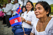 "01 FEBRUARY 2013 - PHNOM PENH, CAMBODIA: A Cambodian mourner with the national flag watches the funeral procession of former King Norodom Sihanouk in Phnom Penh. Norodom Sihanouk (31 October 1922 - 15 October 2012) was the King of Cambodia from 1941 to 1955 and again from 1993 to 2004. He was the effective ruler of Cambodia from 1953 to 1970. After his second abdication in 2004, he was given the honorific of ""The King-Father of Cambodia."" Sihanouk died in Beijing, China, where he was receiving medical care, on Oct. 15, 2012. His cremation is will be on Feb. 4, 2013. Over a million people are expected to attend the service.    PHOTO BY JACK KURTZ"