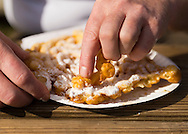 Mill Neck, New York, U.S. 12th October 2013. A visitor is eating fried funnel cakes topped with powdered sugar at the annual Fall Harvest Festival, also known as Apple Fest, which attracts tens of thousands of visitors with its food and more, on the grounds of Mill Neck Manor, an historic Gold Coast estate, during Columbus Day weekend. Proceeds benefit the Mill Neck Family of organizations including the Mill Neck Manor School for the Deaf.
