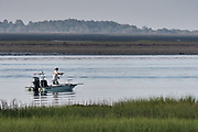 A flats fisherman casts a fly rod from a small boat in the salt marshes of the Cape Romain National Wildlife Refuge near Charleston, South Carolina. The 66,287 acre National Wildlife Refuge encompass water impoundments, creeks, bays, emergent salt marsh and barrier islands most of which is only accessible by boat.