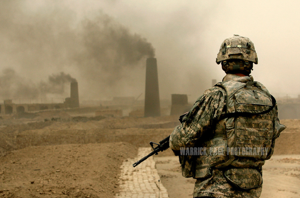 A US soldier with 2nd Brigade, 1st Armored Division, stands on top of a brick kiln overlooking more that 150 collective brick factories at the Narwan brick factory, July 1, 2008 in Narwan, Iraq. Twenty miles east of Baghdad, the 170+ small brick factories employ about 30,000 Iraqis, shaping mud into bricks and fire them in kilns burning heavy fuel oil that produces acrid, black smoke visible from satellite imagery 50 miles above the earth's surface. The brick factory employs seasonal workers, many of whom are children - some are as young as four - in highly toxic conditions offering minimal food and water. Respiratory problems are common amongst the workers and children, with no medical personal available to treat them. (Photo by Warrick Page)