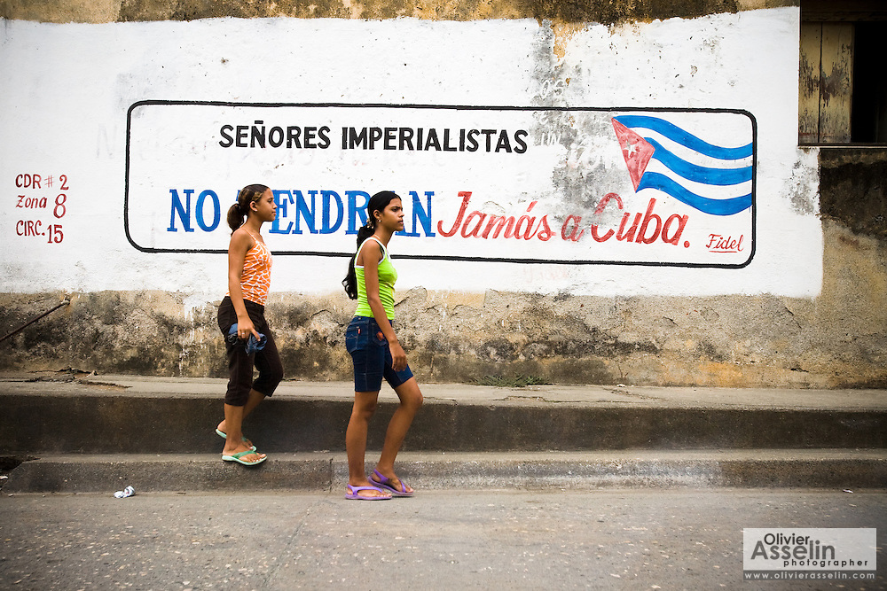 Two teenage girls walk by a wall painting saying, in Spanish : Imperialists sirs, you will never get Cuba, in Baracoa, Cuba on Thursday July 10, 2008.