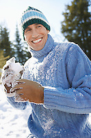 Man wearing winter clothing holding snowball portrait