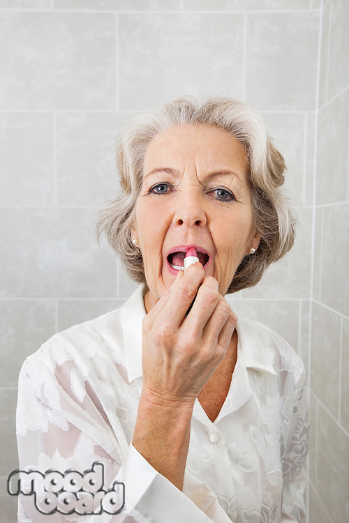 Portrait of senior woman applying lipstick in bathroom