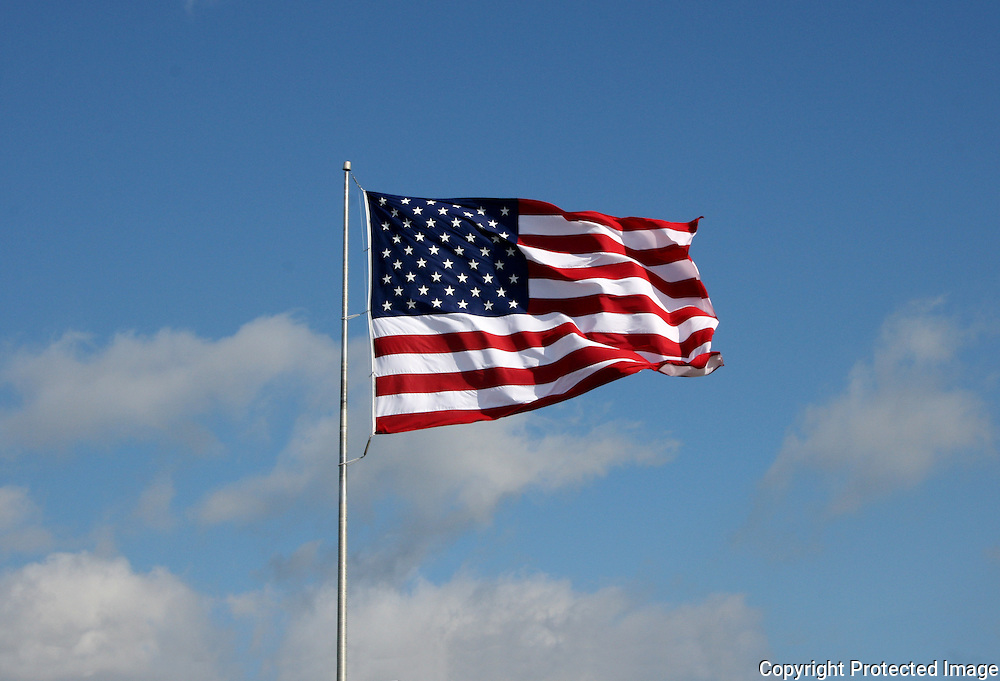 A large American Flag flying proudly under a crisp, blue, summer sky.
