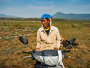 02 APRIL 2016 - NA SAK, LAMPANG, THAILAND: A Thai man on his motorscooter near the original site of Sobjant village. The village of Sobjant in Na Sak district in Lampang province was submerged when the Mae Chang Reservoir was created in the 1980s. The village was relocated to higher ground a few kilometers from its original site. The drought gripping Thailand drained the reservoir and the foundations of the Buddhist temple in the original village became visible early in 2016. Thai families come down to the original village to pray in the ruins of the temple and look at what's left of the village.      PHOTO BY JACK KURTZ