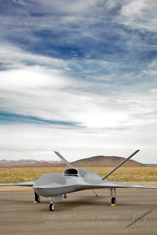 "General Atomics P46 Predator 'C', ""Avenger"" sits on the ramp at Grey Butte Airfield. The latest generation Predator is a jet-powered remotely-piloted vehicle (RPV) that is nearly twice the size of its predecessor. Featuring an internal weapons bay, retractable gear, a blended wing design, top-mounted intake and shielded exhaust, the stealthy airframe can cruise at 50,000 feet and can perform multiple tasks from reconnaisance to attack roles."