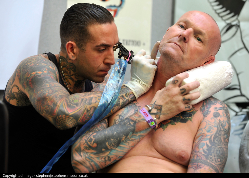 © Licensed to London News Pictures. 23/09/2011. LONDON, UK. A man has a tattoo imprinted on his neck. The 7th London Tattoo convention takes place today (23 Sept 2011) at the Tobacco Dock in the East End of London. The convention attracts artists and customers from all over the world. It runs until 25th September 2011. Photo credit:  Stephen Simpson/LNP