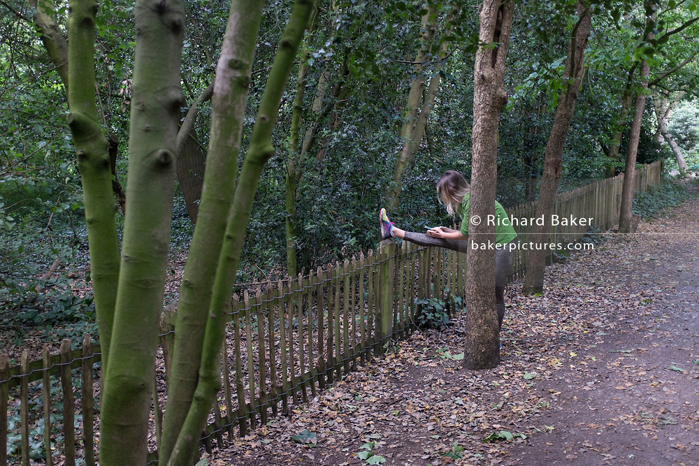 A lady runner stretches while using her phone in Holland Park, on 28th June 2020, in London, England.