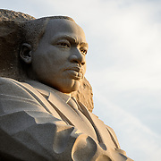 The golden early morning sun moments after sunrise catches the statue of Martin Luther King Jr at the MLK Memorial on the Tidal Basin in Washington DC. Strong side light.