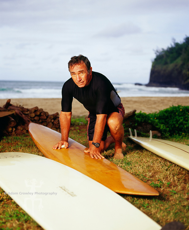 Mature man waxing surfboard, portrait