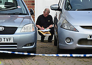 © Licensed to London News Pictures. 13/04/2013. Ruislip, UK A police officer looks at the cars in the drive. Police and ambulance crews at the scene where a woman and two children have been found dead at a house in Ruislip, West London. Police were called by London Ambulance Service at approx 1840 hrs on Friday 12 April to reports of a woman and two children found deceased at an address in Midcroft Road. Photo credit : Stephen Simpson/LNP