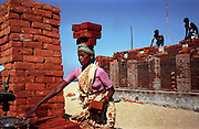 A woman loads bricks on her head as she and other workers rebuild a toilet in a village near Chennai, on the tsunami-hit southeastern coast of India..The December 26, 2004 tsunami killed thousands of people along this coast, smashing boats, roads and houses and tearing thousands of families apart. .Picture taken February 2005 in Nagapptinam, Tamil Nadu, India, by Justin Jin