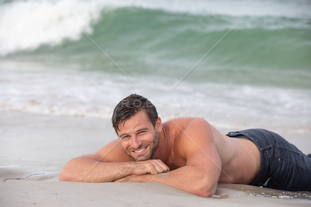 sexy man without a shirt in jeans relaxing in the ocean