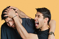 Young male friends playfighting over colored background
