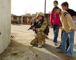 Soldier from the East and West Riding Regiment, Territorial Army, wearing desert camouflage, Kevlar helmet and body armor, carrying SA80 assault rifle which are fitted with SUSAT sights on foot patrol through the streets of Basra during Op Telic in March 2005 is watched by local children
