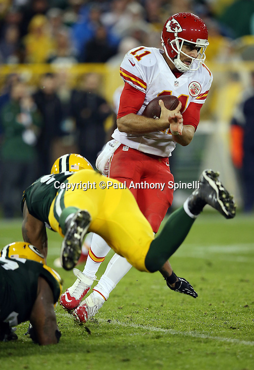 Kansas City Chiefs quarterback Alex Smith (11) gets tackled by Green Bay Packers defensive end Mike Daniels (76) and Green Bay Packers outside linebacker Julius Peppers (56) on a fourth quarter keeper during the 2015 NFL week 3 regular season football game against the Green Bay Packers on Monday, Sept. 28, 2015 in Green Bay, Wis. The Packers won the game 38-28. (©Paul Anthony Spinelli)