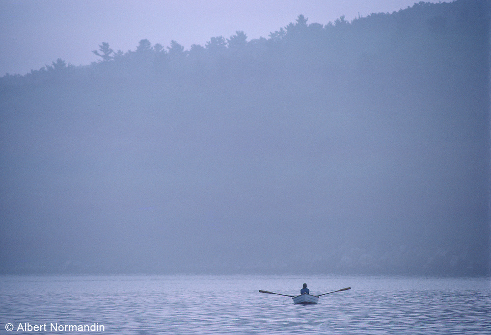 Boat in morning blue mist on lake