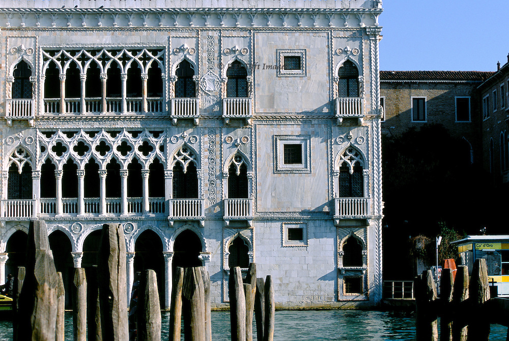 Restored Ca' d'Oro facade, on the Grand Canal, Venice., seen from across the canal through a forest of wooden mooring poles.  On the right, part of the Ca d'Oro vaporetto stop..