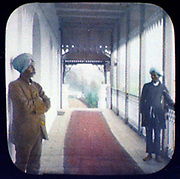 Two turbaned servantswaiting on the wooden verandah of a white-painted  stucco building, possibly India.  Hand-coloured magic lantern slide, 1895.