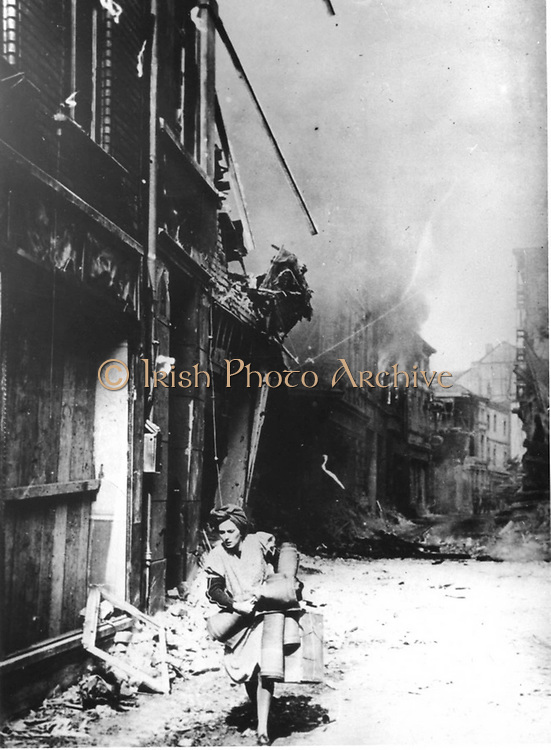 In a German town in 1945 a woman flees after explosions rock the buildings.