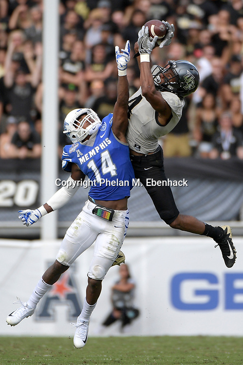 Central Florida wide receiver Tre'Quan Smith (4) catches a 40-yard pass in front of Memphis defensive back Jonathan Cook (14) during the first half of the American Athletic Conference championship NCAA college football game Saturday, Dec. 2, 2017, in Orlando, Fla. (Photo by Phelan M. Ebenhack)