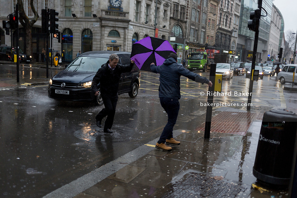 Storm Georgina swept across parts of Britain and in central London, lunchtime office workers were caught out by torrential rain and high winds, on 24th January 2018, in London, England. Pedestrians resorted to leaping across deep puddles at the junction of New Oxford Street and Kingsway at Holborn, the result of overflowing drains. Sixth in a sequence of seven photos.