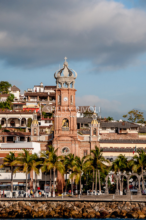 Our Lady of Guadalupe church and the old town Malecon of Puerto Vallarta seen from the water, with people walking the malecon with palm trees.