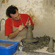 Man forming clay on a potters wheel at a ceramics factory in Deruta, Italy