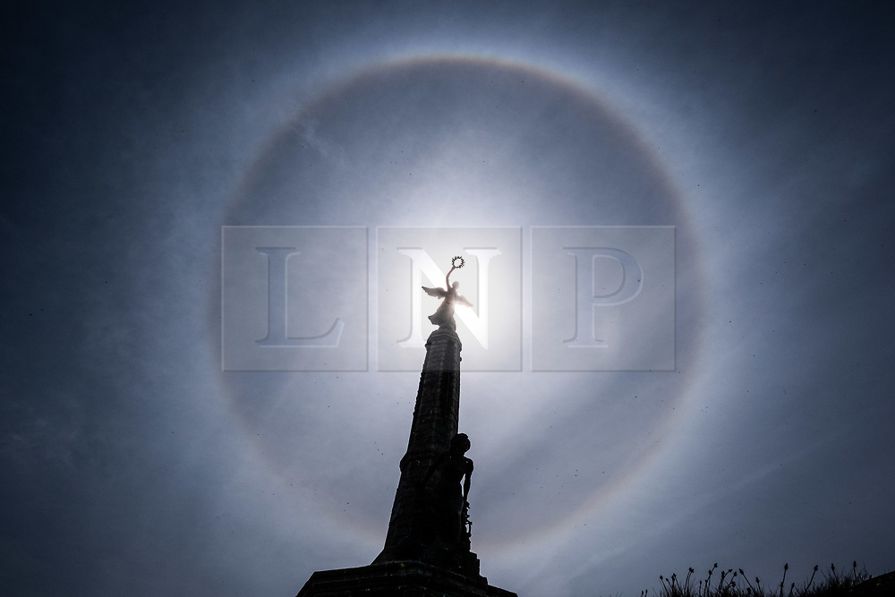 © Licensed to London News Pictures. 15/05/2019 Aberystwyth, UK. A man and his dog arr silhouetted as perfect circular sun halo , formed as the rays of the sun shine through ice crystals in the upper atmosphere, fills the sky above Aberystwyth. The halos, always at 22º from the sun, often indicate that rain will fall within the next 24 hours, since the cirrostratus clouds that cause them can signify an approaching frontal system. The weather is set to change overnight from the fine warm conditions to cooler and wetter days, more typical of mid May. Photo credit Keith Morris/LNP