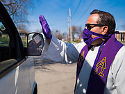 "05 APRIL 2020 - DES MOINES, IOWA:  Rev. RUSSELL LACKEY blesses a person after a drive through Palm Sunday service sponsored by Luther Memorial Church on the campus of Grand View University in Des Moines. About 150 people attended the service. They remained in their cars while the ministers read a short passage from the Bible, handed out palms and blessed them. On Sunday, 05 April, Iowa reported 868 confirmed cases of the Novel Coronavirus (SARS-CoV-2) and COVID-19. There have been 22 deaths attributed to COVID-19 in Iowa. Restaurants, bars, movie theaters, places that draw crowds are closed until 30 April. The Governor has not ordered ""shelter in place"" but several Mayors, including the Mayor of Des Moines, have asked residents to stay in their homes for all but essential needs. People are being encouraged to practice ""social distancing"" and many businesses are requiring or encouraging employees to telecommute.       PHOTO BY JACK KURTZ"
