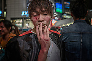 Man adjusts his fangs in the throng that builds at the Shibuya Crossing in Tokyo on Halloween.  Tokyo, Japan.