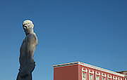 Statue at the Stadio dei Marmi or Stadium of the Marbles, a stadium designed c. 1928 by Enrico Del Debbio and inaugurated 1932, at the Foro Italico, Rome, Italy, and behind, the CONI building (Comitato Olimpico Nazionale Italiano). The stadium has Carrara marble steps lined by 59 marble statues of athletes in classical style. The Foro Italico or Foro Mussolini is a sports complex built 1928-38 in Fascist style by Enrico Del Debbio and Luigi Moretti, inspired by Roman forums. Fascist architecture developed in the late 1920s and 1930s, as a modernist style in times of nationalism and totalitarianism under Benito Mussolini. It is characterised by large, square, symmetrical buildings with little or no decoration, often inspired by ancient Rome and designed to convey strength and power. Picture by Manuel Cohen