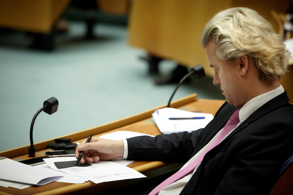 Nederland. Den Haag, 26 april 2012. <br /> Geert Wilders tijdens debat over gesloten principe-akkoord. Het formulier met de sprekers tekent hij zwart.....<br /> VVD, CDA, D66, GroenLinks en ChristenUnie zijn met het kabinet een principe-akkoord overeengekomen over de begroting van volgend jaar.<br /> Men is als Tweede Kamer uit de impasse gekomen om voor mei een begroting voor 2013 op te stellen na de val van het kabinet Rutte van VVD, CDA en met gedoogsteun van de PVV van Geert Wilders. Crisisakkoord na mislukken ook van Catshuisberaad. 3% Financieringstekort.<br /> Het kabinet en de regeringspartijen VVD en CDA hebben in twee politiek gezien krankzinnige dagen met de oppositiepartijen D66, GroenLinks en de ChristenUnie een akkoord gesloten over bezuinigingen en hervormingen in 2013. Minister Jan Kees de Jager van Financi&euml;n koppelde als verkenner de vijf partijen aan elkaar en kreeg in nog geen 30 uur voor elkaar waar VVD en CDA met gedoogpartij PVV in 7 weken overleg in het Catshuis niet in waren geslaagd. Politiek, kabinet Rutte, kabinetscrisis, Catshuisonderhandelingen, Tweede Kamer, <br /> Foto : Martijn Beekman