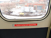 Do not lean against door text sign on a subway train wagon door.