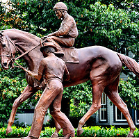 Secretariat Sculpture at Kentucky Horse Park by Edwin Bogucki in Lexington, Kentucky<br /> Secretariat was perhaps the greatest racehorse in history. In 1973, he shattered the records in the Triple Crown: the Preakness Stakes, the Kentucky Derby and the Belmont Stakes. In that last race, he won by 31 lengths. A tribute to this magnificent horse of owner Penny Chenery is at the Kentucky Horse Park in Lexington, Kentucky. The sculpture by Edwin Bogucki shows the legendary thoroughbred with his jockey Ron Turcotte. Standing alongside is his groomer, Eddie Sweat. The statue captures the moment after winning the Kentucky Derby at Churchill Downs in May of 1973. Remarkably, Secretariat ran each of the five quarter miles faster than the previous ones.