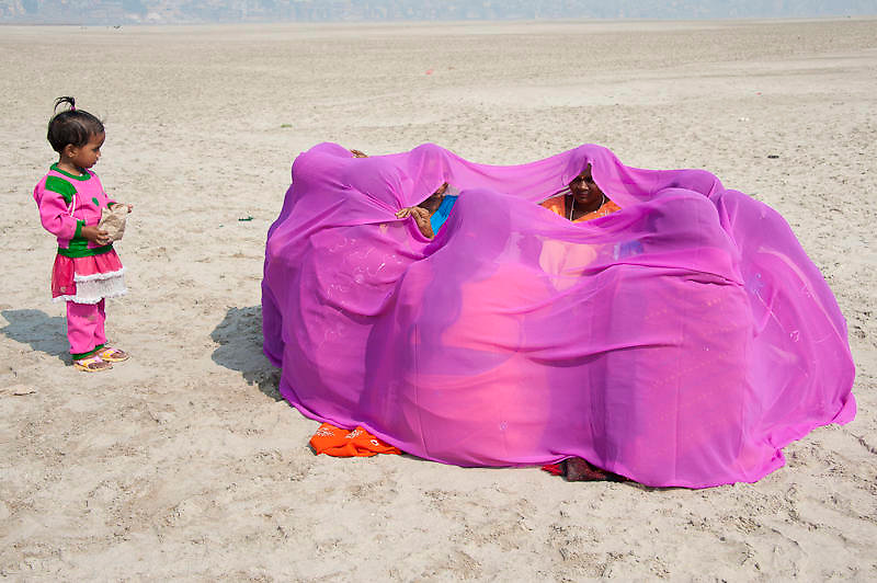 Group of Indian women hiding under a pink sari, Varanasi (India)