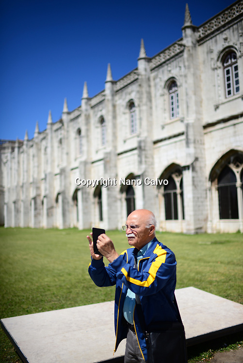 Mature man taking photos with smartphone at The Jeronimos Monastery or Hieronymites Monastery (The Mosteiro dos Jeronimos), a former monastery of the Order of Saint Jerome near the Tagus river in the parish of Belém, in the Lisbon Municipality, Portugal