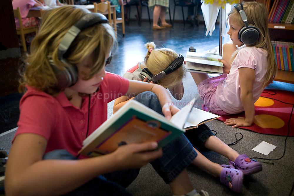 30/5/2008 basisschool De Braskorf , Veendam, taal-leeslokaal. Lisanne, Esther en Anouk lezen en luisteren mbv koptelefoon.  foto: Pepijn van den Broeke. kilometers: 73