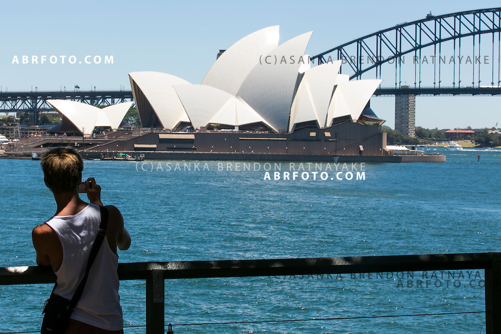 Tourist takes a photo of the Sydney Harbour with the Sydney Harbour Bridge and Opera house in the background viewed from the Royal Botanic Gardens
