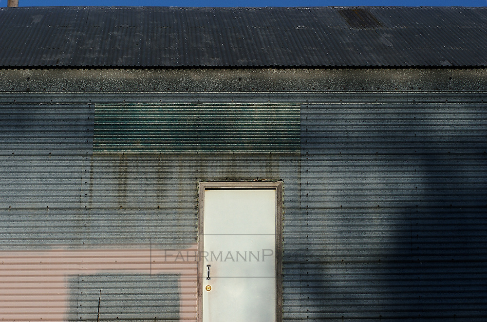 Abstraction of a corrugated steel building with a white door