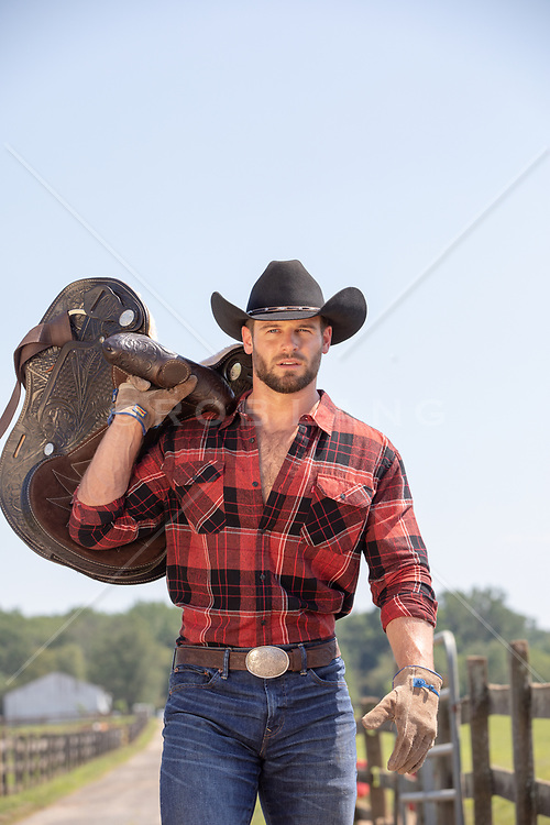 cowboy carrying a saddle on a ranch