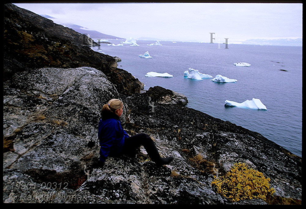 Young woman sits on granite ledge overlooking fjord and icebergs near Uummannaq Island; Qilakitsoq, northwest Greenland.