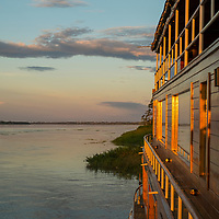 View of the sunset and the Delfin II ship on the Yanayacu River. Pacaya Samiria National Reserve, Upper Amazon, Peru.