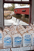 Sacks of cornmeal for sale line up in Bridgeton Mill, by a window view of the Bridgeton Covered Bridge, dam and spillway, in Bridgeton Historic District, Parke County, Indiana, USA. Bridgeton Mill was established 1823, rebuilt 1870, and is the oldest continuously operating mill west of the Allegheny Mountains. The mill grinds wheat into flour and corn into meal with 200 year-old French Buhr stones. The red-painted Bridgeton Covered Bridge (245 feet long) was rebuilt in historically accurate Burr Arch style in 2006 over Big Raccoon Creek (replacing 1868 bridge burnt by arson in 2005).